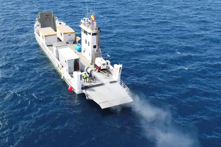 An aerial shot of a large boat in the ocean carrying a canon spraying mist into the sky.