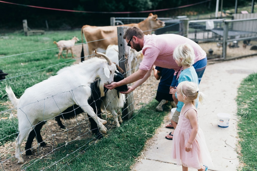 Man and young children feed goats.