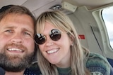 A man and a woman pose for a selfie on board a plane