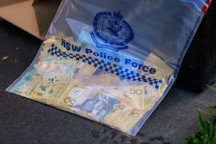 A pile of $50 notes and some $100 notes in a clear plastic bag with the NSW Police Force logo.