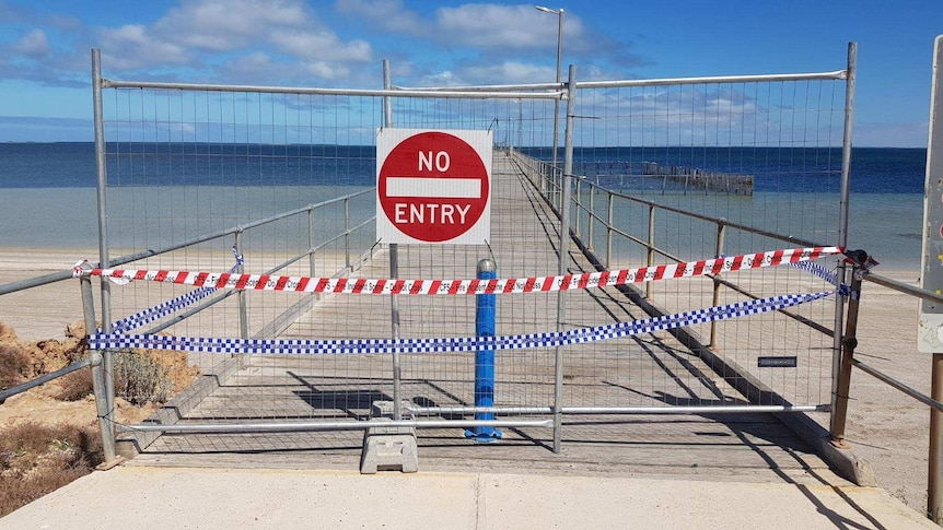 """A """"no entry"""" sign blocks access to a long jetty."""