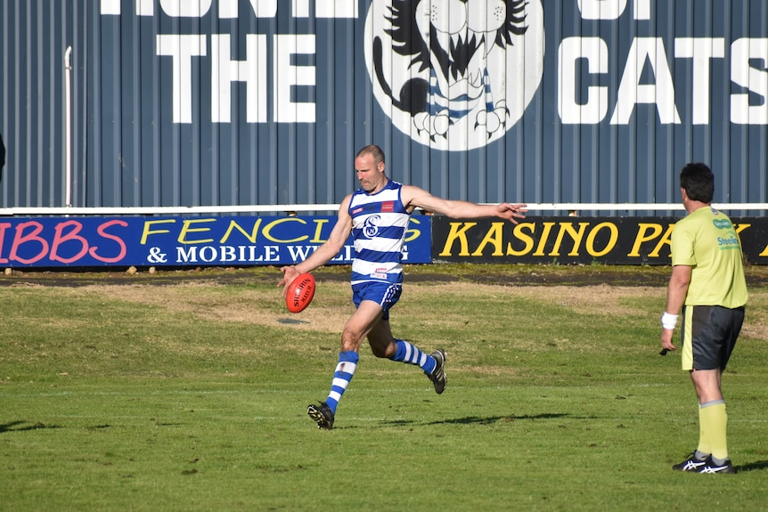A man in a blue and white striped football jersey and blue shorts kicks a football, umpire standing next to him