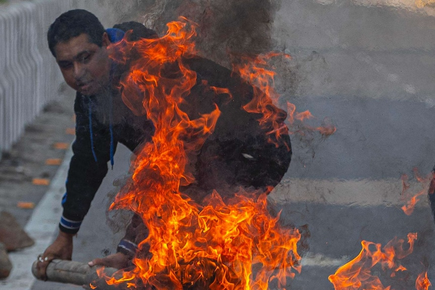 A protestor sets a fire in the middle of the road to block traffic in India.