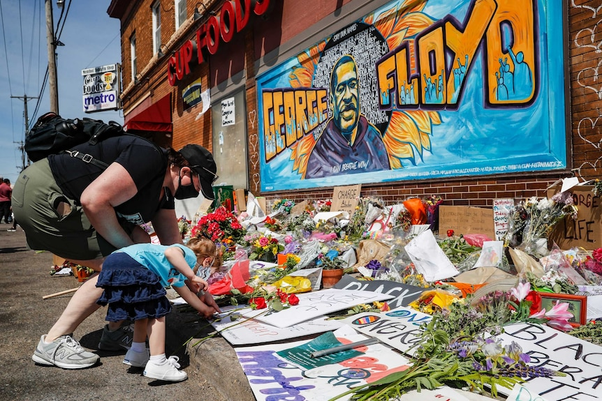 A woman and child add to a floral tribute in front of a mural of George Floyd