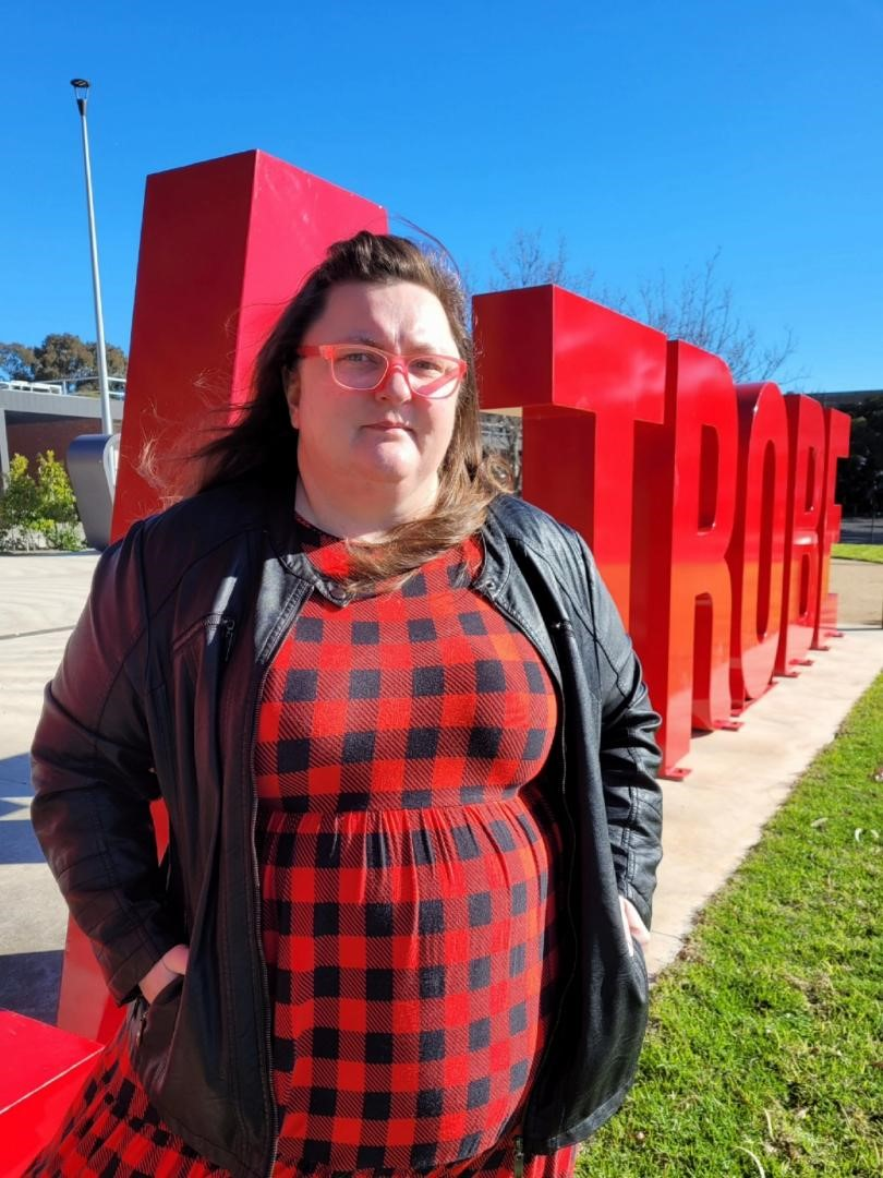 A woman wearing a red and black checked dress and red glasses stands defiantly in front of a red la trobe sign.