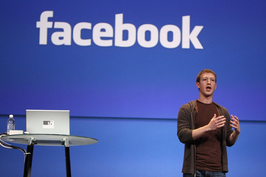 Facebook CEO Mark Zuckerberg talking to an audience with a Facebook sign behind him