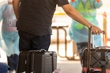 A man and a woman roll there luggage past people in PPE after arriving in Darwin from India.