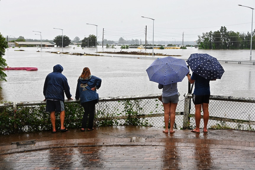 people in the rain looking at a bridge that has been submerged