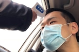 A man in a mask in a car is checked with a thermometer, being held through his car window.