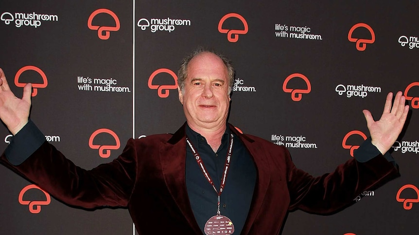 Michael Gudinski with his hands in the air starting in front of a Mushroom Group sign