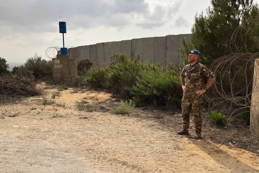 A guard stands at the Blue Line wall