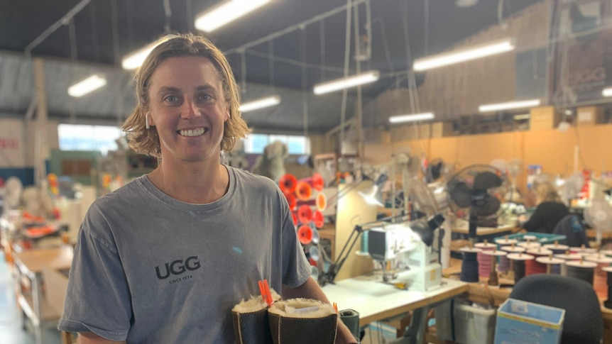 Ugg Director Todd Watts smiling holding ugg boots at Burleigh Heads factory