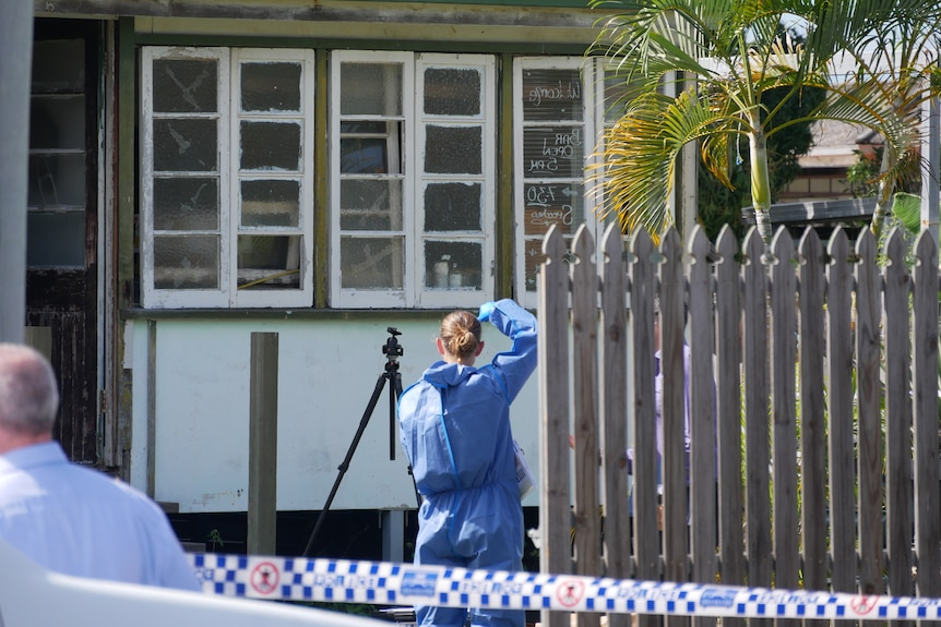 A police officer, wearing blue overalls, takes a photograph of a house