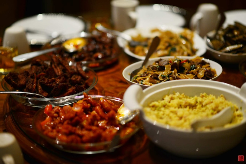 Plates with different dishes of Chinese food in them