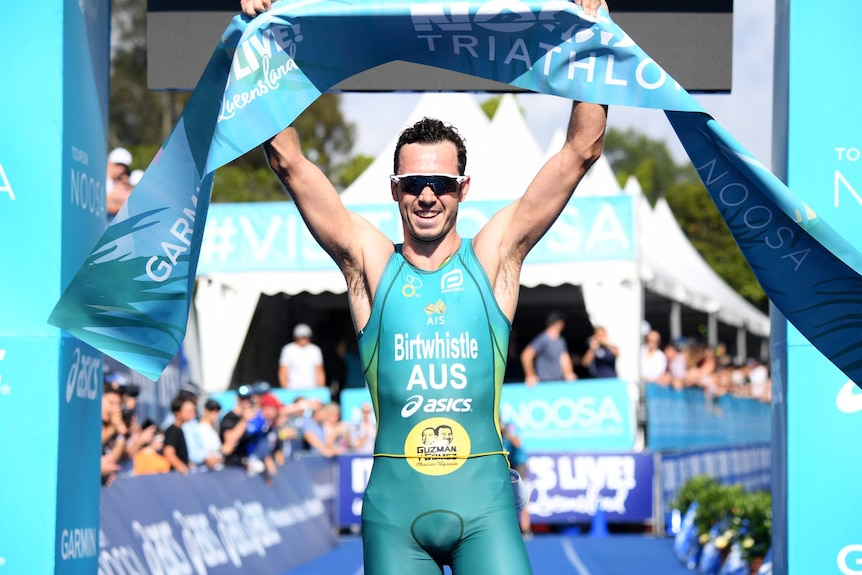 An athlete, wearing sunglasses and a skintight suit, raises his arms in victory as he crosses the line.
