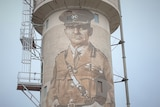 Water tower with man painted on it