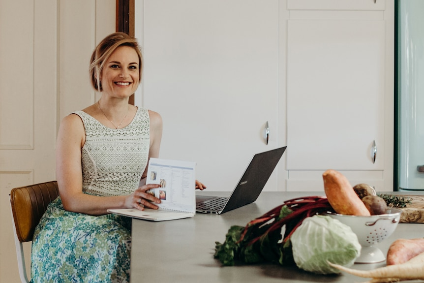 A woman sits at a kitchen table with a book and laptop open in front of her.