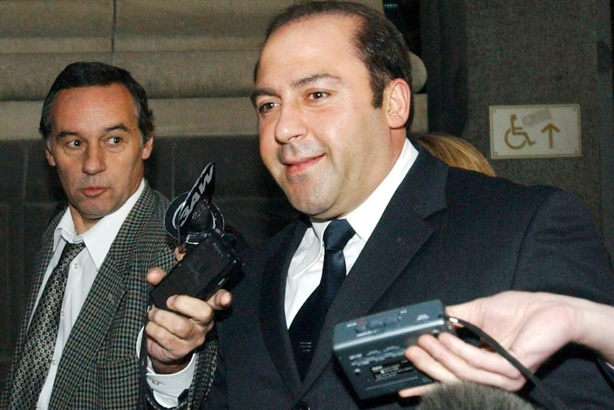 Tony Mokbel, wearing a suit, smiles as reporters hold microphones in front of his face.