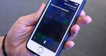 A close-up of a woman's hand holding onto an iPhone as she speaks to Siri.