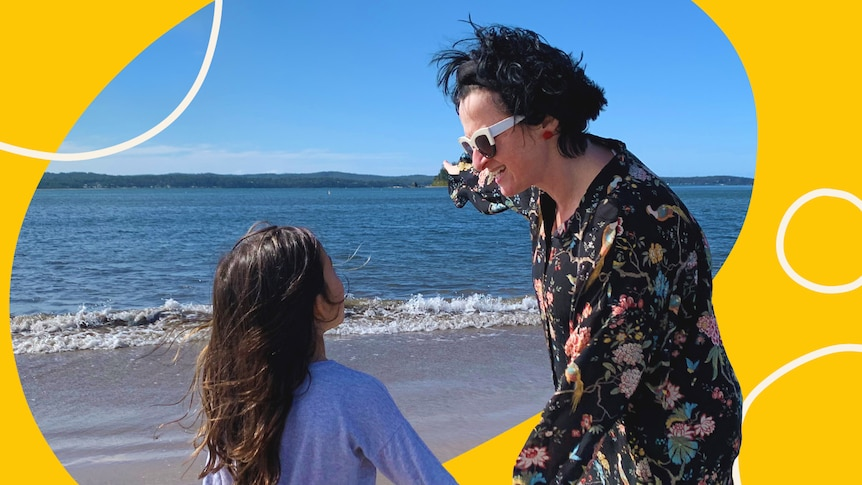 A woman and child hold hands on a beach for story on helping children accept their skin colour