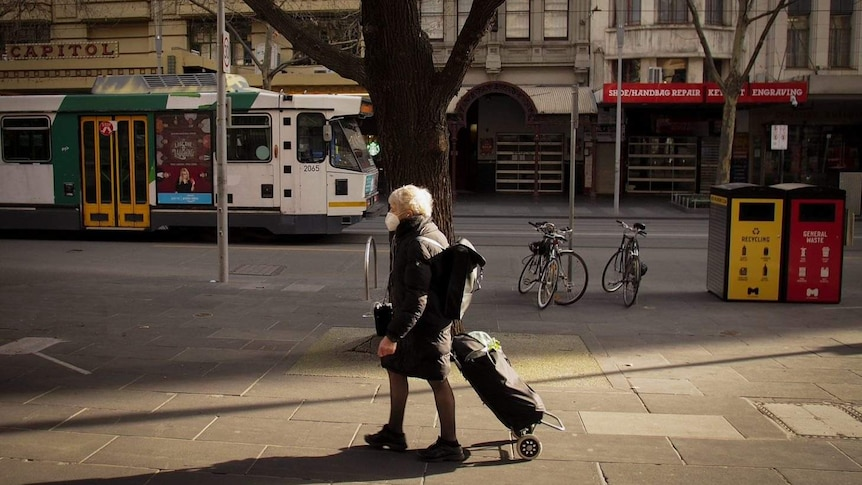 A woman wearing a face mask walks in Melbourne's CBD. A tram can be seen in the background.