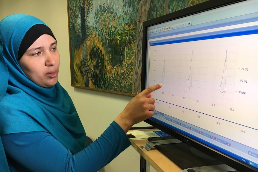 A woman studies a line graph on a computer screen.