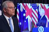 Australian Prime Minister Scott Morrison speaks at a podium while US President Joe Biden appears on a TV screen.