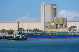 A freight ship docked in the Port of Townsville with a tug boat in the foreground and silos in the background