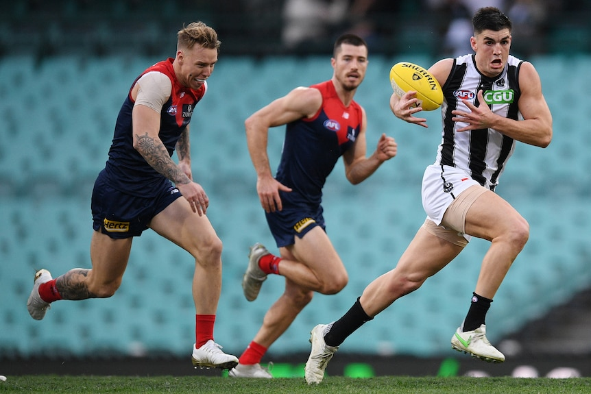 A Collingwood AFL player runs the ball while being chased by two Melbourne opponents.