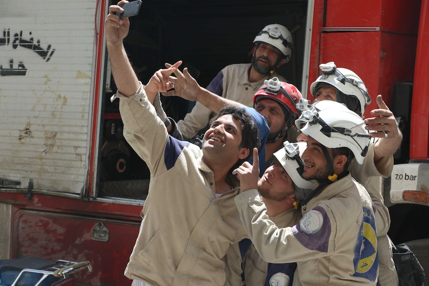 You view a crowd of men in white helmets and in beige work uniforms posting for a smartphone selfie.