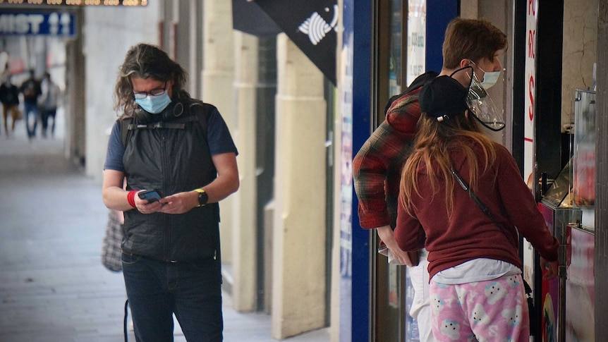 Customers in masks queue outside a shopfront in Sydney lockdown.