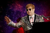 Singer Elton John performs on stage sitting at a piano