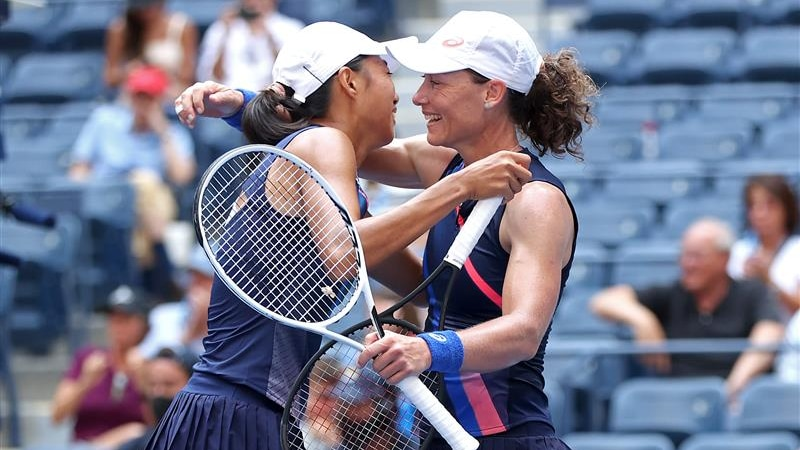 Two smiling women's doubles players embrace, with Sam Stosur holding her racquet in one hand after winning the US Open.