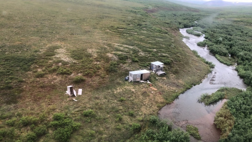 Three ramshackle buildings in the wilderness near a river.