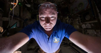 Scott Kelly holds the camera in front of him and takes a selfie with his spectacles on his head.