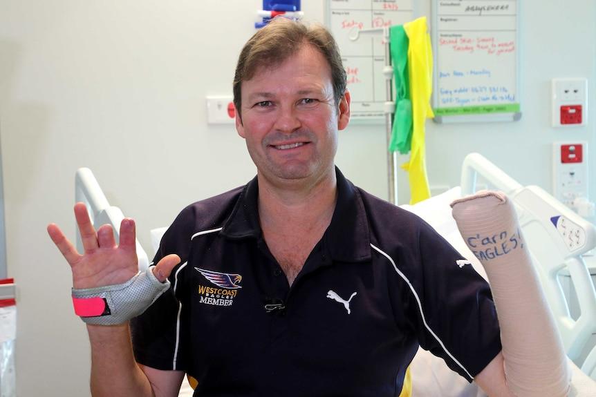 A man in a West Coast Eagles t-shirt sits on a bed holding up his hands, one with two fingers missing and another bandaged