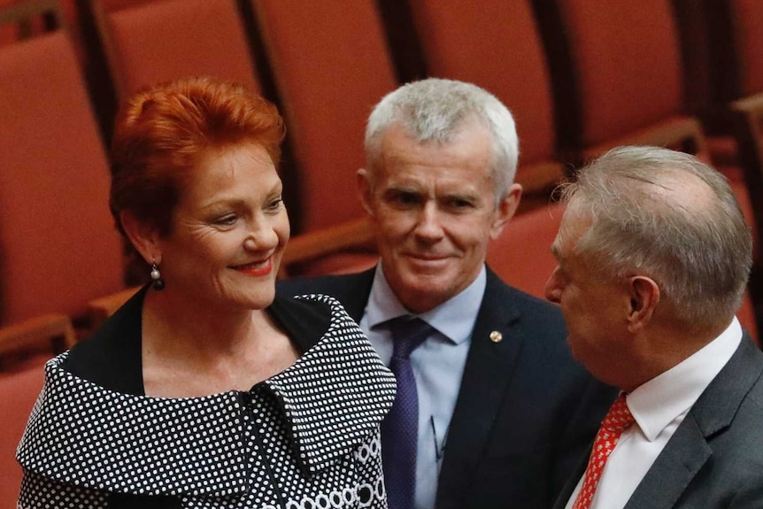 A red haired woman talks with two old white men in the Senate