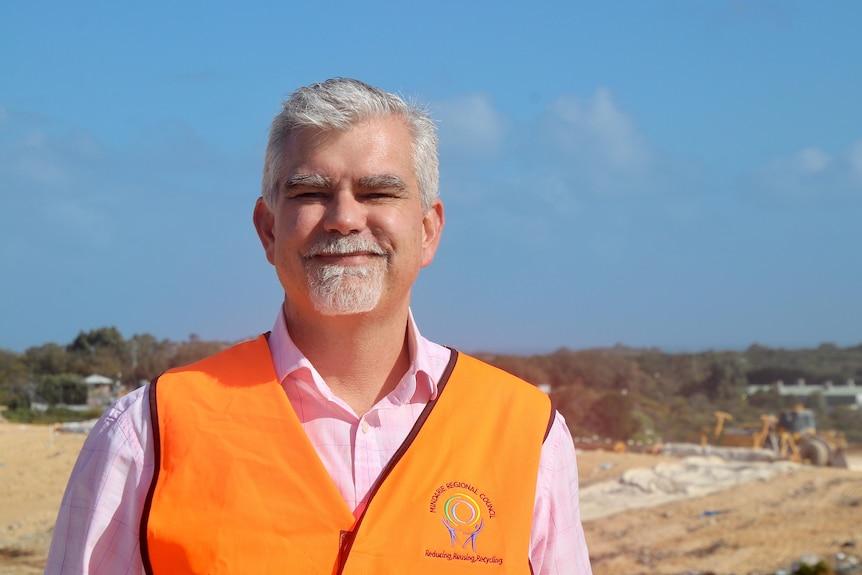 A close-up photo of Gunter Hoppe wearing a high vis orange vest.