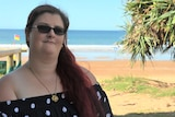A woman with red hair sits in her wheelchair with the beach in the background.