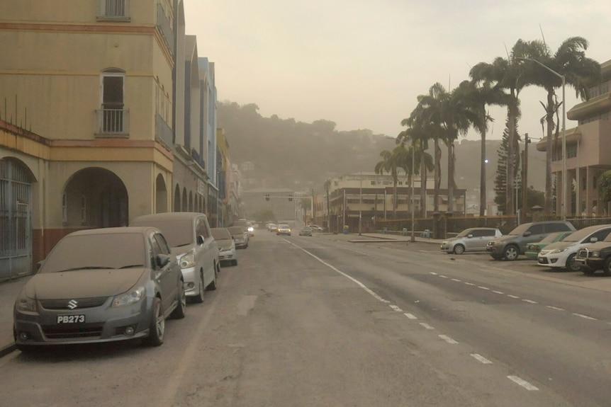 O stradă de oraș cu mașini acoperite de cenușă și aer tulbure.