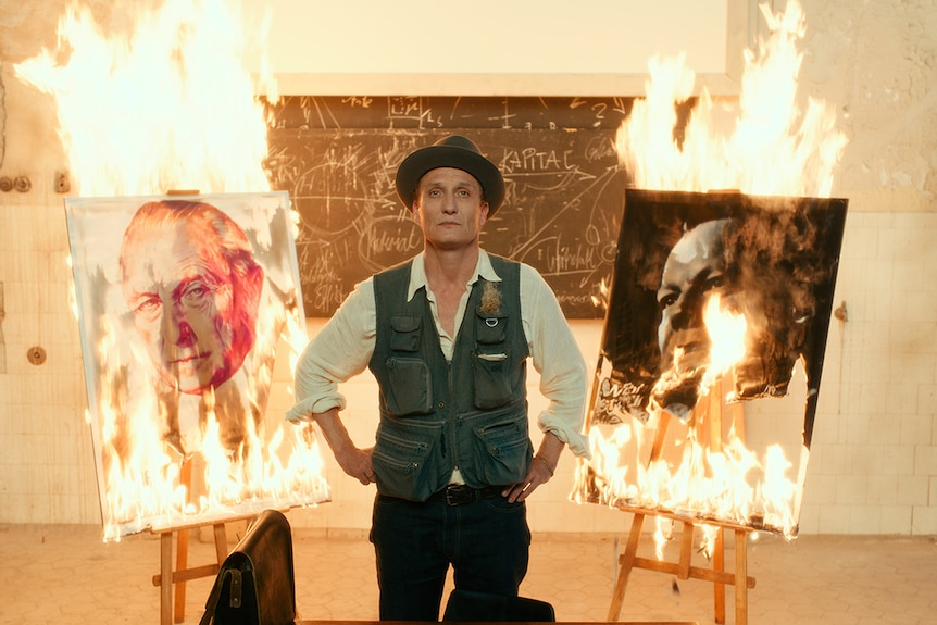 Colour still of Oliver Masucci standing between two burning paintings in white room in 2018 film Never Look Away.