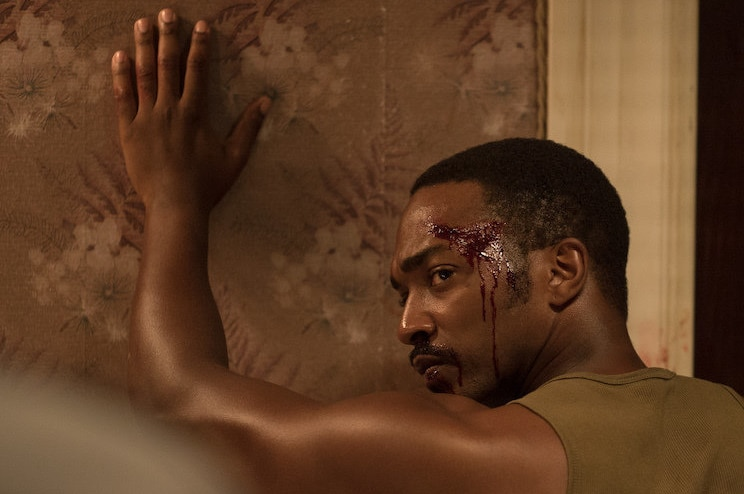 Still image from 2017 film Detroit of actor Anthony Mackie with his hands against the wall and head bloodied.