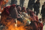 Tibetan Buddhist monks throw the body of an earthquake victim on the fire of a mass cremation