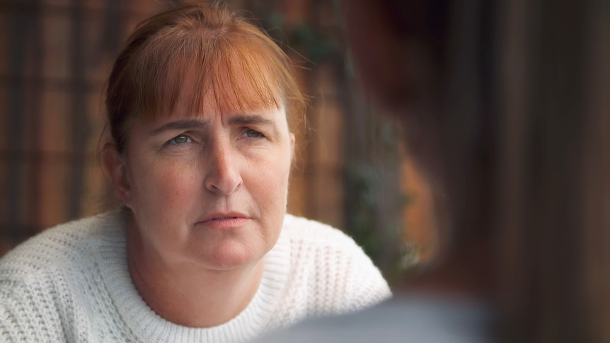 A woman with a short fringe looks serious as she speaks with an unidentifiable person.