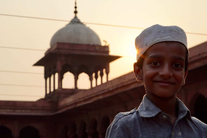 Young boy stands in front of a mosque as the sun sets.
