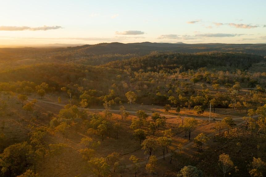 An aerial shot of the sun setting behind a vast open plain.