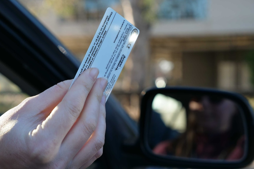 A hand holds a driver's licence out a car window.