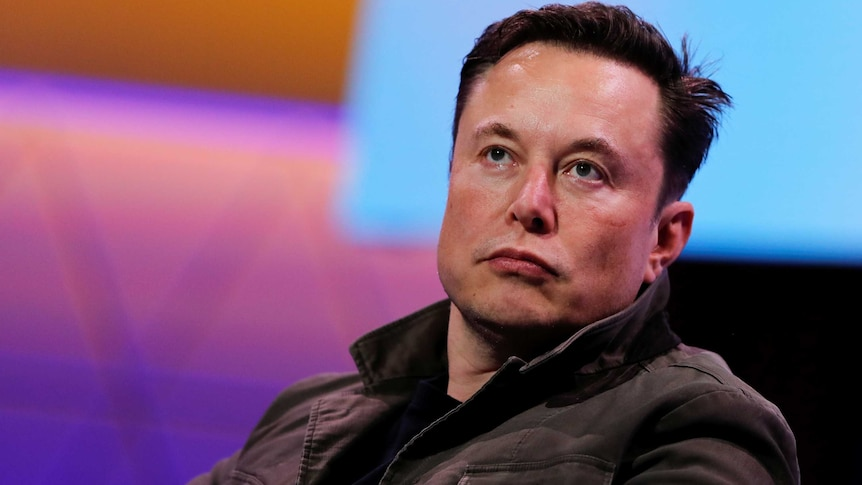 A close up of Elon Musk's face. He is unsmiling and appears to be concentrating on a person off-camera.