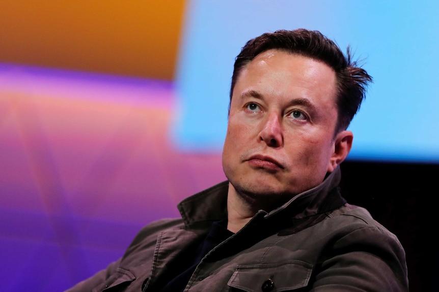 Primo piano del volto di Elon Musk.  Non sta sorridendo e sembra concentrarsi su qualcuno fuori dalla telecamera.