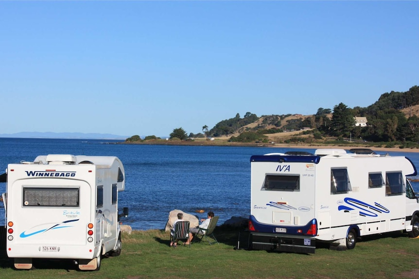 A couple look out over a beach sitting next to two motorhomes.